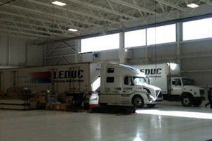 White floors and walls with gleaming white transport units highlight the Leduc Truck Service Warehouse