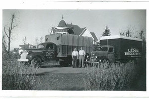 A decades-old picture of two men in shirtsleeves stand proudly in front their 40's era truck fleet.
