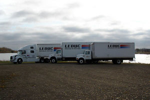 Two shiny, new, white freight trucks with a matching tractor-trailer unit in the background is part of the Leduc Truck Service modern fleet.