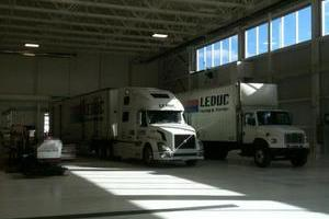 Stark white floors and walls with gleaming white transport units highlight the Leduc Truck Service Warehouse
