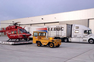 A Stars Air Ambulance helicopter rests on a steel skid awaiting loading onto a Leduc Truck Service semi unit.